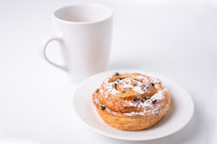 Sweet bun with raisins and cup of coffee or tea over white Royalty Free Stock Photos