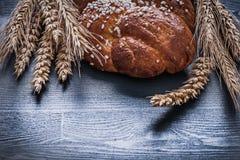Sweet bun  wheat ears on board Stock Photo