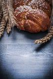 Sweet bun and wheat ears on board Stock Photography