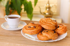 Sweet buns  with raisins and a cup of tea on the table Stock Images