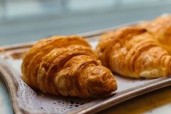 Sweet butter croissant on a lace paper. Tray on a window shop of a Baker shop. royalty free stock images