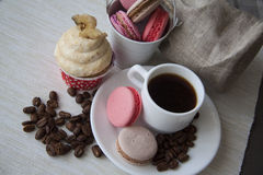 Sweet buttercream cupcake and coffee on chequered tablecloth Royalty Free Stock Images