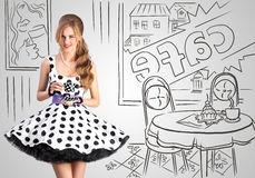 Sweet cafe. Creative vintage photo of a beautiful pin-up girl in a polka-dot dress in a cafe, holding a cup of tea on sketchy interior background Royalty Free Stock Image