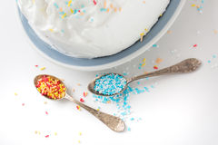 Sweet cake with blue, yellow, red and white sprinkles. Sweet cake with blue and white sprinkles on teaspoon Stock Image