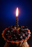 Sweet cake with candle on blue Stock Images