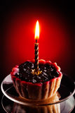 Sweet cake with candle on red Royalty Free Stock Images