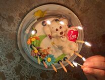 Sweet cake with candles. A hand holds a match with fire for lighting candles on cake.