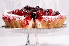 Sweet cake with cherry jelly, tasty and fresh on a white shabby wooden background royalty free stock photography