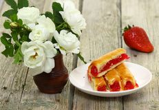 Sweet cake with strawberry. Dessert - sweet cake with strawberry on a plate with red background Stock Image