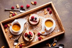 Sweet cakes with berries on table close-up with cup of espresso royalty free stock image