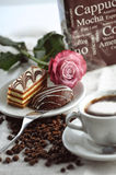 Sweet cakes with coffee beans, cup of coffee and box with letters on table, product photography for patisserie or coffee shop with Royalty Free Stock Photo