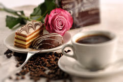 Sweet cakes with coffee beans and cup of coffee on table, product photography for patisserie or coffee shop Stock Images