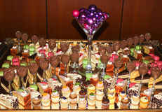 Sweet cakes and dessert banquet. Banquet table filled with sweet cakes and desserts including chocolate mousse, cheesecake, macaroons Stock Image