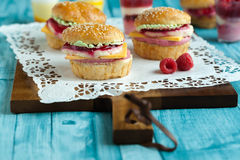 Sweet cakes in the form of a burger. Sweet cake in the form of a burger, strawberry mousse with white chocolate and roll with sesame seeds, cooking background Stock Photography
