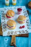 Sweet cakes in the form of a burger. Sweet cake in the form of a burger, strawberry mousse with white chocolate and roll with sesame seeds, cooking background Royalty Free Stock Images