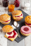 Sweet cakes in the form of a burger. Sweet cake in the form of a burger, strawberry mousse with white chocolate and roll with sesame seeds, cooking background Stock Photo
