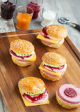 Sweet cakes in the form of a burger. Sweet cake in the form of a burger, strawberry mousse with white chocolate and roll with sesame seeds, cooking background Royalty Free Stock Photos