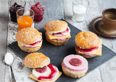Sweet cakes in the form of a burger. Sweet cake in the form of a burger, strawberry mousse with white chocolate and roll with sesame seeds, cooking background Stock Image