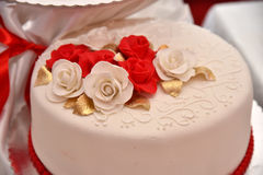 Sweet cakes in the form of red roses decorate the wedding cake with more decorative twigs of white cream. Photographed at a wedding in Novi Sad, Serbia Royalty Free Stock Photos