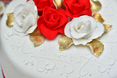 Sweet cakes in the form of red roses decorate the wedding cake with more decorative twigs of white cream. Photographed at a wedding in Novi Sad, Serbia Royalty Free Stock Image