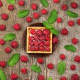 Sweet cakes with fresh raspberries. On rough wood background Royalty Free Stock Photos