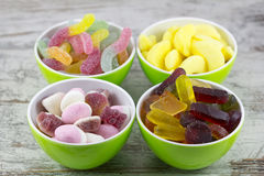 Sweet candies. In four green bowls royalty free stock images