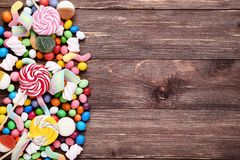 Sweet candies and lollipops. On brown wooden table stock image