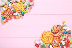 Sweet candies and lollipops. On pink wooden table royalty free stock images