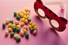 Sweet candies scattering on the pink background with children`s carnival mask. Top view. Holiday concept. Colorful jellybeans candy with carnival mask on pink royalty free stock image