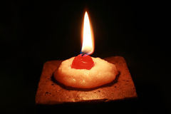 Sweet candle. Beautiful candle as a cake, crowned a waxen cherry Stock Image