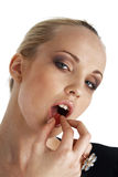 Sweet Candy. Close-up portrait of young blond model eating a candy over white Stock Photos