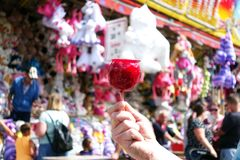 Sweet candy apple on county fair or festival. red candy apple covered in red caramel, at holiday vacation event or amusement park. Sweet candy apple on county stock images