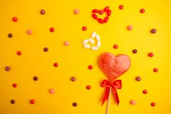 Sweet candy background with sweet heart over yellowe background. Flat lay, overhead view Royalty Free Stock Photo
