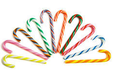Sweet candy-canes. Colorful candy-canes in a row on a white background Royalty Free Stock Images