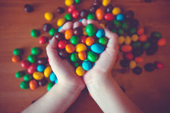Sweet candy. Child's hands holding a handful of chocolates royalty free stock photo