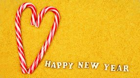 Sweet candy santa claus staff in the shape of a heart with lette. Rs, the text of a happy new year on a bright yellow background for the new year and Christmas Stock Images