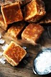 Sweet caramel candies.  Salted caramel pieces and sea salt close Royalty Free Stock Photography