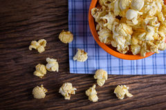 Sweet caramel popcorn in a bowl on blue cotton napkin against wo Royalty Free Stock Photos