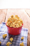 Sweet caramel popcorn in a bowl on blue cotton napkin against wo Stock Images