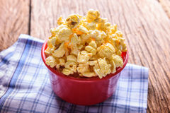 Sweet caramel popcorn in a bowl on blue cotton napkin against wo Stock Photography