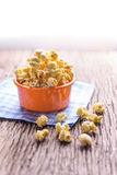 Sweet caramel popcorn in a bowl on blue cotton napkin against wo Royalty Free Stock Photo