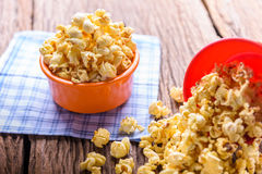 Sweet caramel popcorn in a bowl on blue cotton napkin against wo Stock Photos