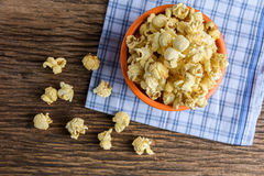 Sweet caramel popcorn in a bowl on blue cotton napkin against wo Royalty Free Stock Image