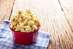 Sweet caramel popcorn in a bowl on blue cotton napkin against wo Royalty Free Stock Photography