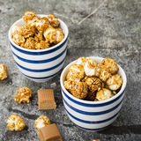 Sweet caramel popcorn in two ceramic white striped blue bowls on a stylish gray stone background. Selective focus. Stock Images