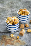 Sweet caramel popcorn in two ceramic white striped blue bowls on a stylish gray stone background. Selective focus. Royalty Free Stock Photography