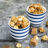 Sweet caramel popcorn in two ceramic white striped blue bowls on a stylish gray stone background. Selective focus. Stock Photo