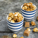 Sweet caramel popcorn in two ceramic white striped blue bowls on a stylish gray stone background. Selective focus. Royalty Free Stock Images