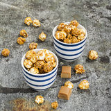 Sweet caramel popcorn in two ceramic white striped blue bowls on a stylish gray stone background. Selective focus. Royalty Free Stock Photo
