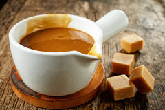 Sweet caramel sauce. Bowl of sweet caramel sauce on old wooden table royalty free stock photography